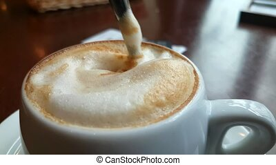 Spoon stirs sugar in a cup with cappuccino