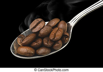 Spoon with coffee beans steaming on the black