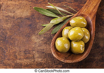 Spoon with green olives