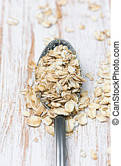 Spoon with oat flakes on white wooden background
