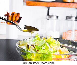 spoon with olive oil and drop on italian fresh salad