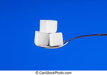 Spoon with white sugar cubes on a blue background