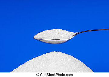 Spoon with white sugar on a blue background