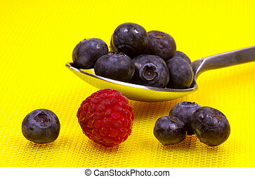 Spoon With Blueberries and a Raspberry