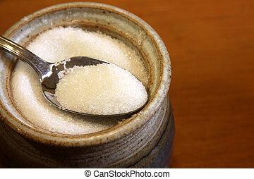 A spoonful of sugar sitting in a bowl of a sugar.