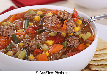 Vegetable soup with hamburger meat on a spoon