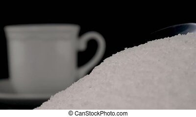 Spoonful of white sugar added in cup of coffee on black...