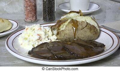 Spooning gravy onto a baked potato slow motion - Ladling...