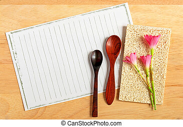 spoons and flowers with paper on wooden background