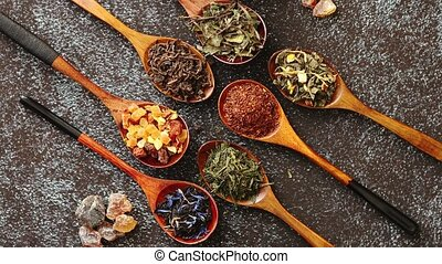 Spoons with different types of dry tea leaves. - Spoons with...
