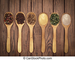 Spoons with spices on a wooden background
