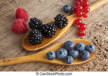 Spoos with berries - Autumn berries and wooden spoons on an...