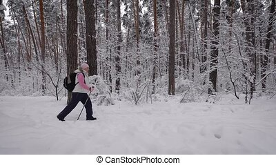 Sport adult woman quickly goes through the woods. Behind her is a backpack.