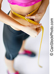 trained belly with measuring tape - sport and diet concept -...