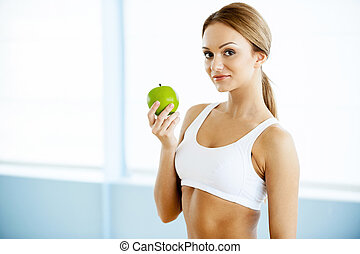 Sport and dieting. Beautiful young woman in sports clothing holding green apple and smiling at camera