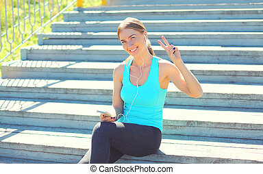 Sport and fitness concept - beautiful smiling young woman listens to music on smartphone in city park