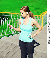 Sport and fitness concept - beautiful young woman listens to music and using smartphone in city park