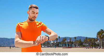 sport and healthy lifestyle concept - man with fitness tracker training outdoors