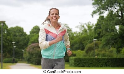 woman with fitness tracker running in park - sport and...