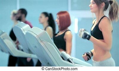 Sport and slender girl walks on a treadmill