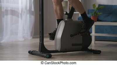 sport at home during self-isolation, male legs are spinning pedals of stationary bicycle in living room, closeup view, training at home, healthy lifestyle