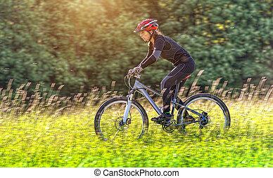 Sport bike woman in a beautiful meadow