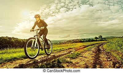 Sport bike woman on a meadow with a beautiful landscape