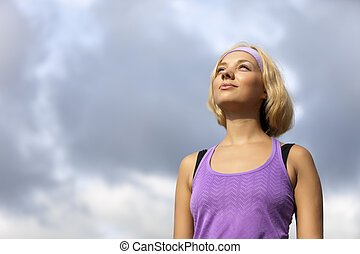 sport blond woman is looking up to the future, freedom