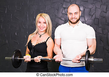 Sport, bodybuilding, gym and people concept - Portrait of sporty couple with barbell smiling at camera