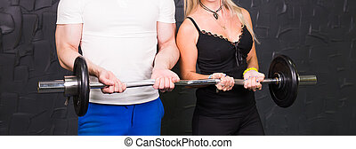 Sport, bodybuilding, lifestyle and people concept - Close up of man and woman with barbell