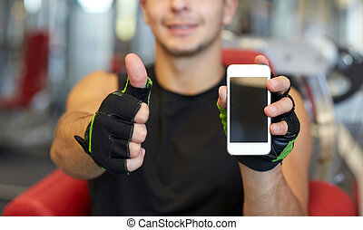 young man with smartphone showing thumbs up in gym