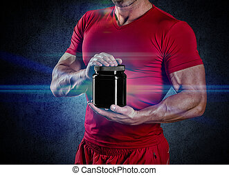 sport, bodybuilding, strength and people concept - young man standing holding jar with protein over dark background