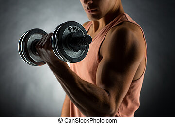 close up of young man with dumbbell