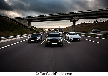 Sport cars racing on the road under the bridge