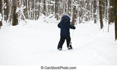 Sport childhood - boy skier slides in winter snow forest
