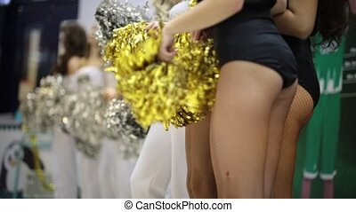 Sport competition. Cheerleading women standing indoors. Legs...