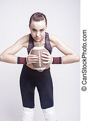 Sport Concept: Sportive Caucasian Female American Football Player with Ball