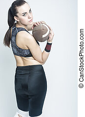 Sport Concepts and Ideas. Professional Female Athlete Posing with American Football Ball. Looking Backwards