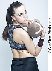 Sport Concepts and Ideas. Professional Female Athlete Posing with American Football Ball. Looking Backwards.