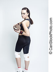 Sport Concepts. Full Length Portrait of Female Caucasian Athlete Posing with American Football Ball. Looking Backwards.Against White.