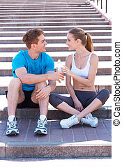 Sport connecting people. Side view of beautiful young couple in sports clothing sitting on stairs face to face and smiling