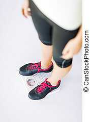woman legs standing on scales - sport, diet and weight loss...