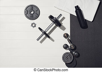 Sport equipment on white wooden background, training at home concept.