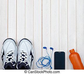 Sport equipment. Sneakers, water, earphones and phone on wooden background
