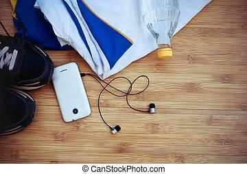 Sport equipment. Sneakers, water, earphones and phone on wooden background.