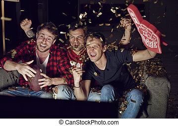 Sport fan cheering among confetti falling