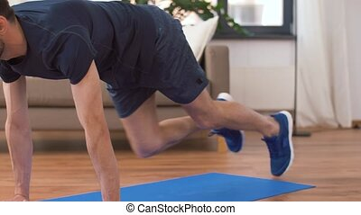 man doing running plank exercise at home - sport, fitness ...