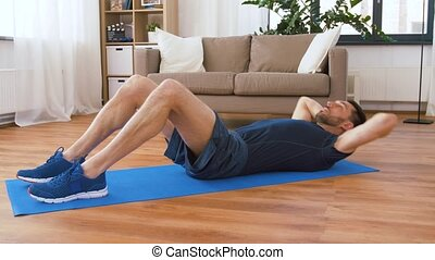 man making abdominal exercises at home - sport, fitness and...