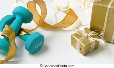 dumbbells and gift boxes on white background - sport,...