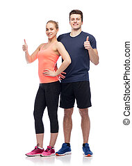 happy sportive man and woman showing thumbs up
